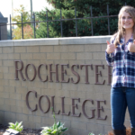 Student with thumbs up in front of Rochester College sign