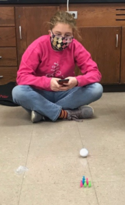 student sitting on floor bowling with technology