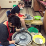 students using pottery wheel